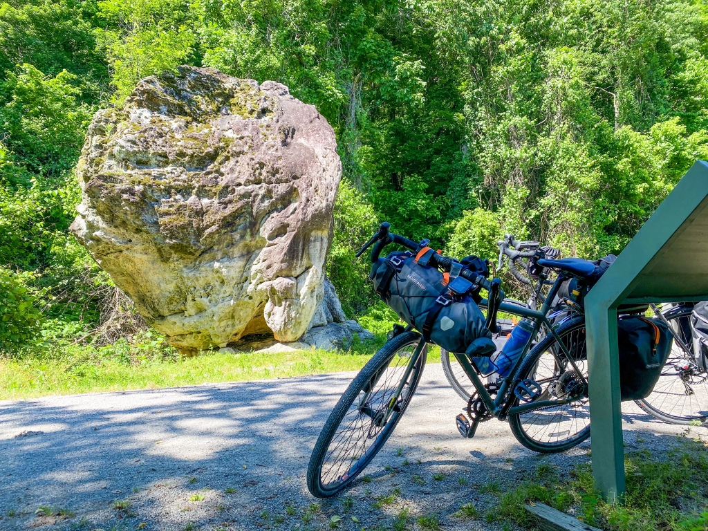 Bike parked in front of large rock formation.